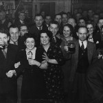 Bar at the PANDO club house, Dorothy King in the middle wearing a patterned dress with husband Arthur King to her right holding up a pint