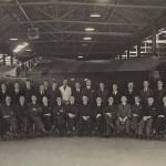 War time photograph of the management team in front of an airframe fabricated on the site